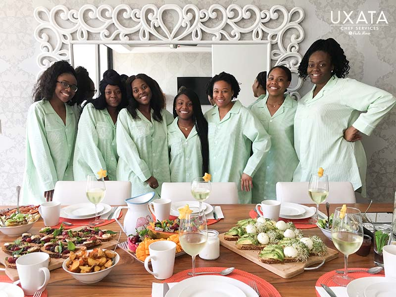 Seven friends celebrating a bachelorette party, standing in front of a table with a buffet, by UXATA Private Chef Services, in Punta Maroma, Riviera Maya, Mexico.