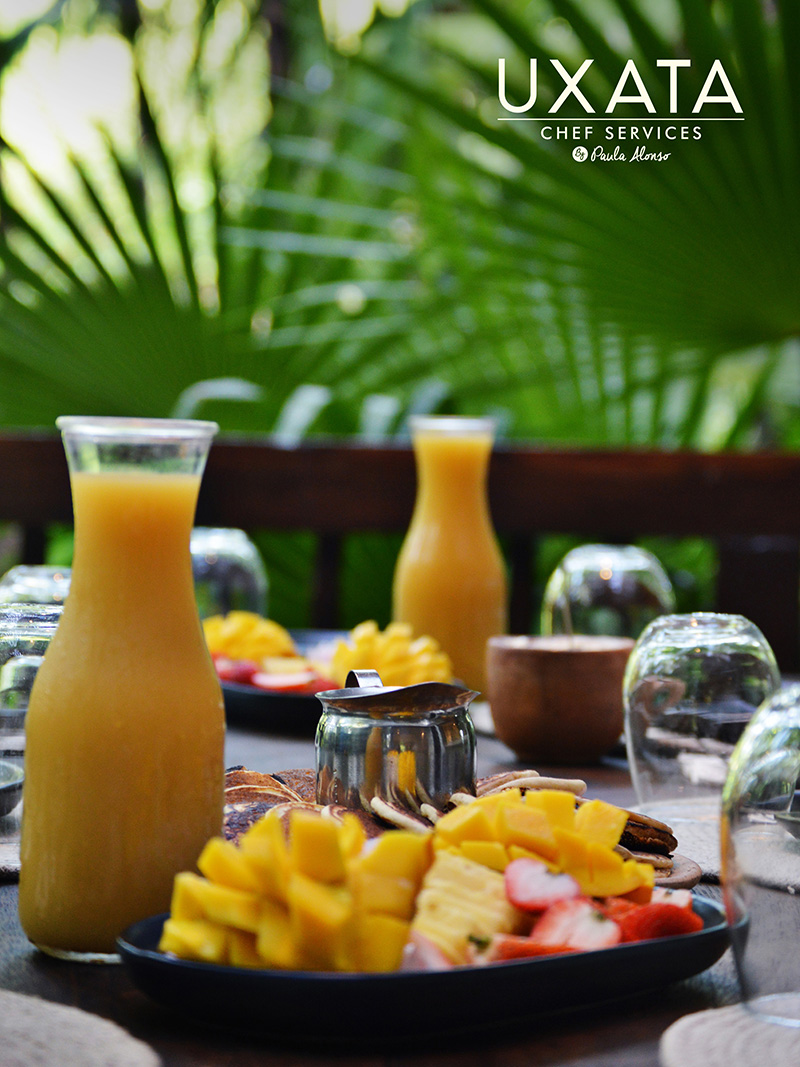 A breakfast with orange and mango juice, tropical fruits, served at the table by UXATA Private Chef Services, Riviera Maya, Mexico.