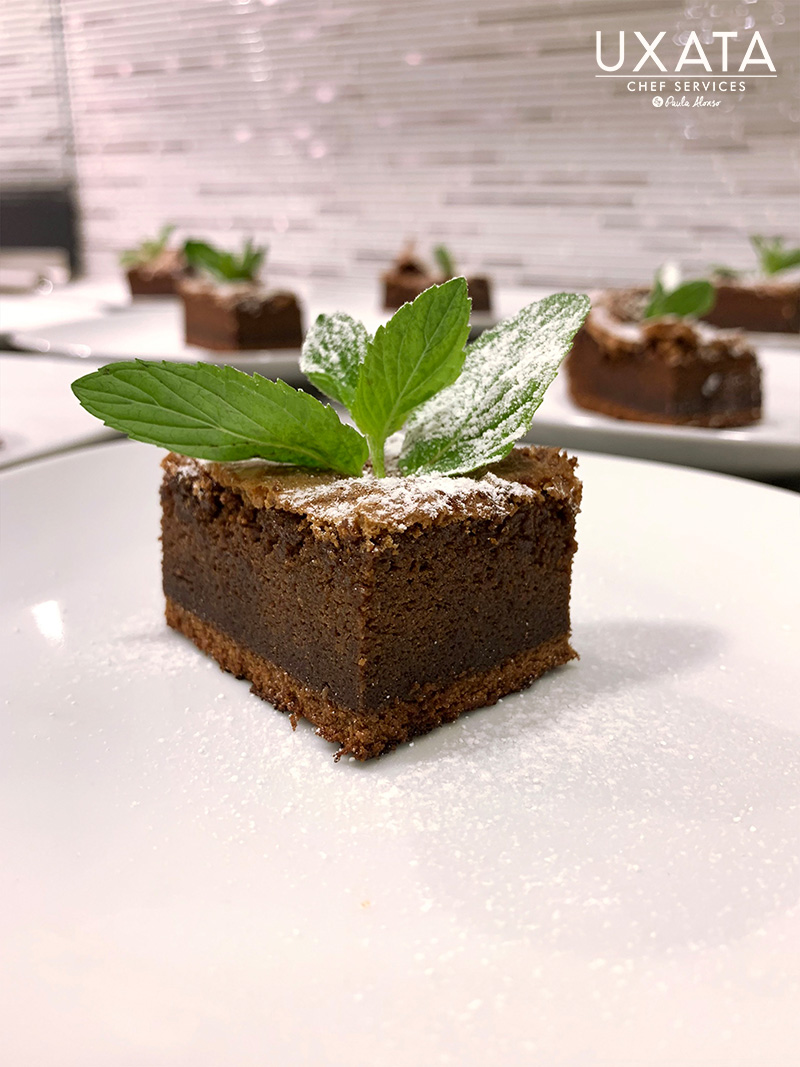 A plate with moist dark chocolate cake and mint leaves by UXATA Private Cook