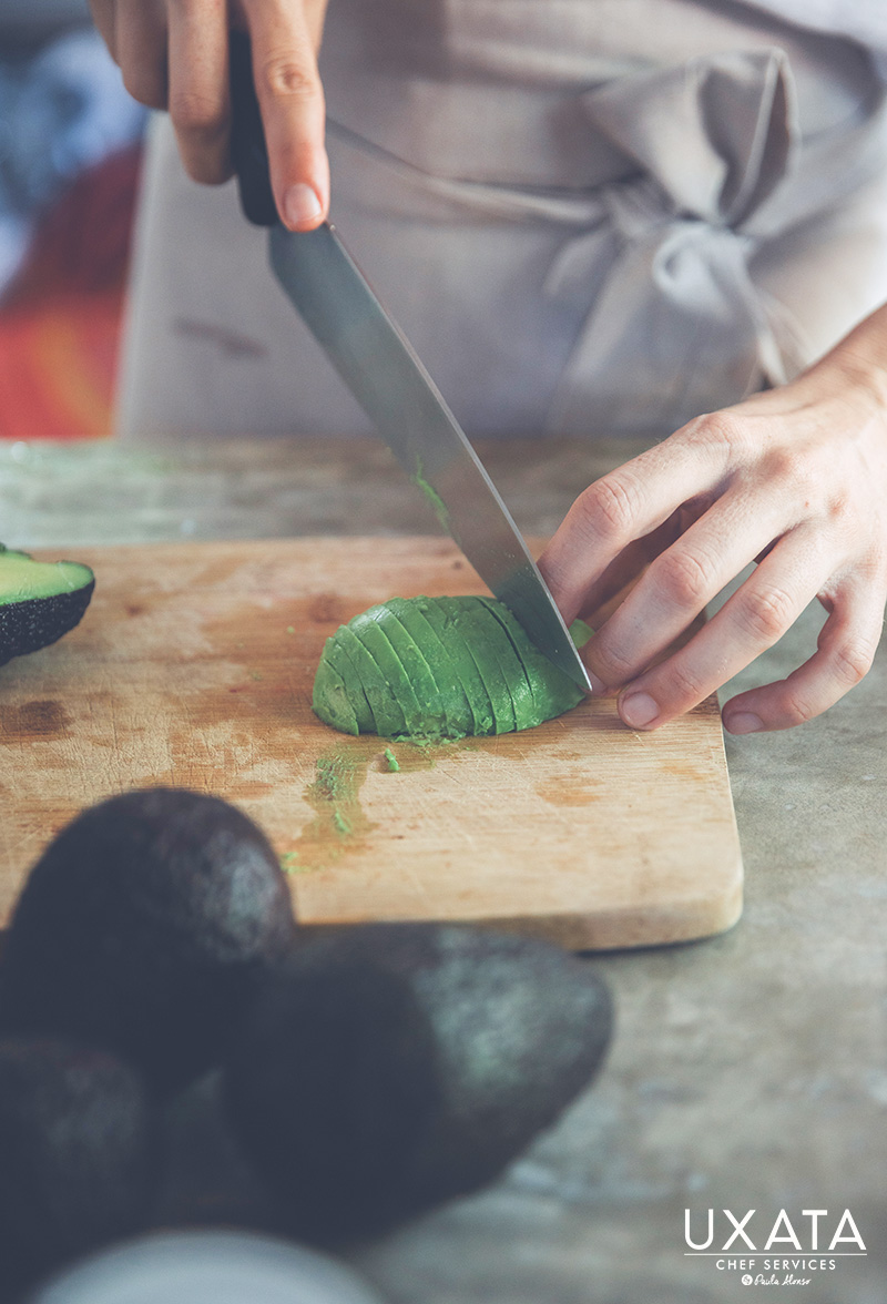 Chef Paula Alonso from UXATA Chef Personal reeling an avocado on a wooden board.