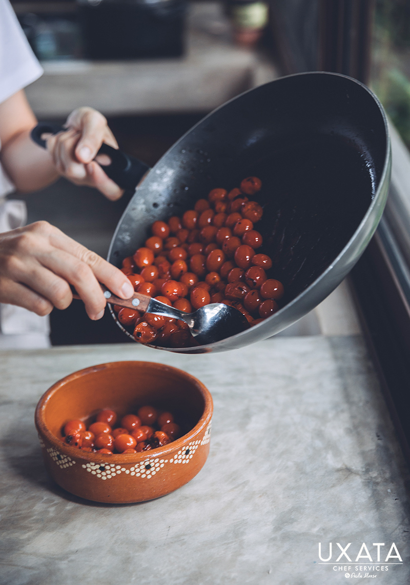 Chef transferring sautéed cherry tomatoes from a frying pan to a bowl.